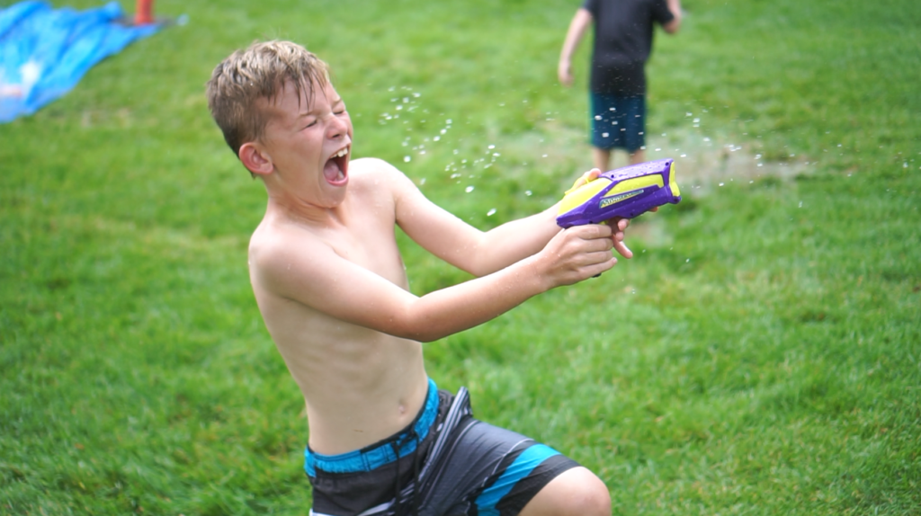 A boy shooting a water gun