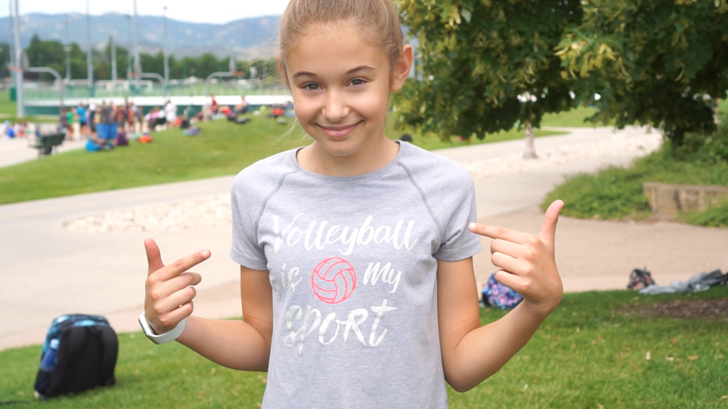 "A girl pointing at her shirt which says ""Volleyball is my sport"""
