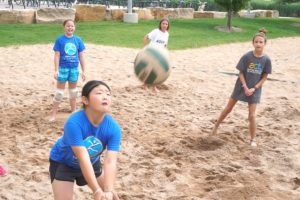 Girls playing volleyball on a sand court