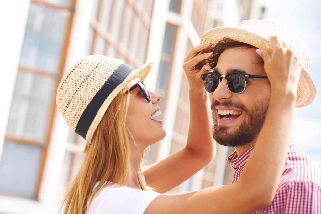 Happy girl and her boyfriend in hats and sunglasses enjoying their being together