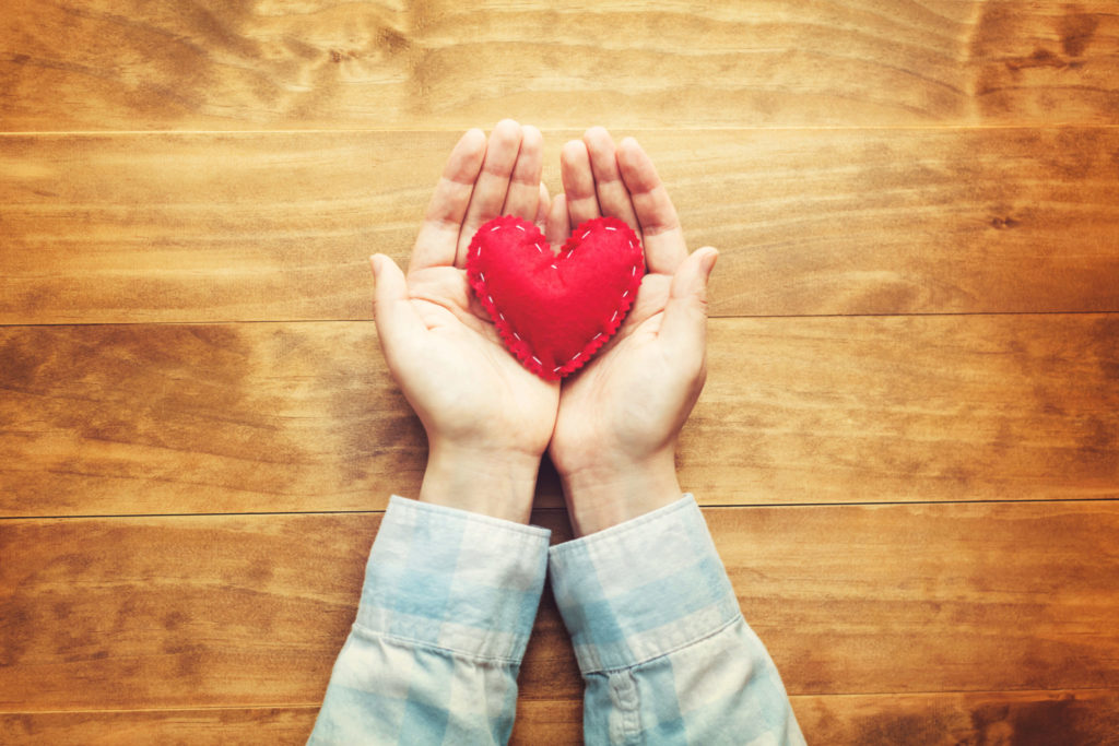 A person holding a hand made red heart in hands.