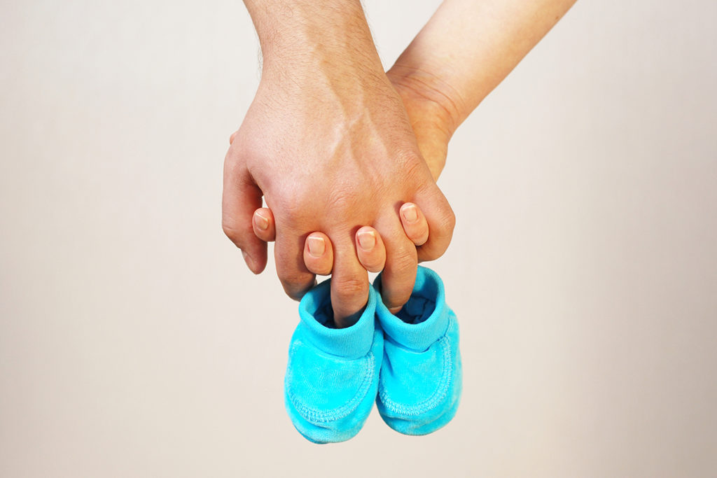 Happy Young Parents Hold In Their Hands Baby Shoes Of Future Child