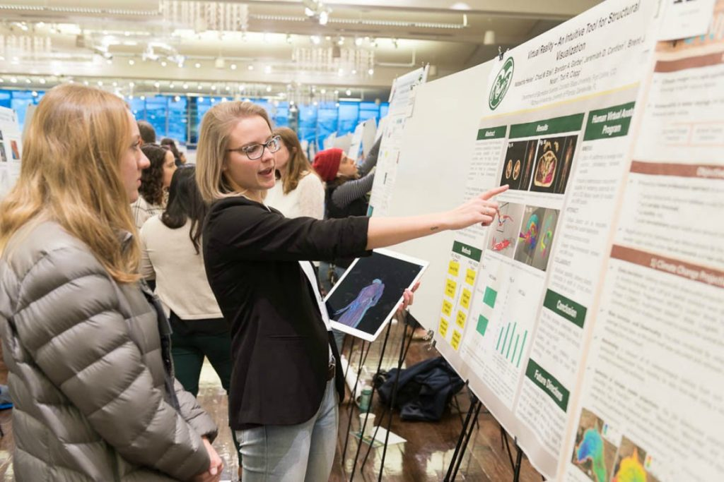 Young woman in black sweater points to her research display poster in the Lory Student Center ballroom.