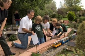 Prue Kaley and Mark Goldrich showing kids the train garden and smiling