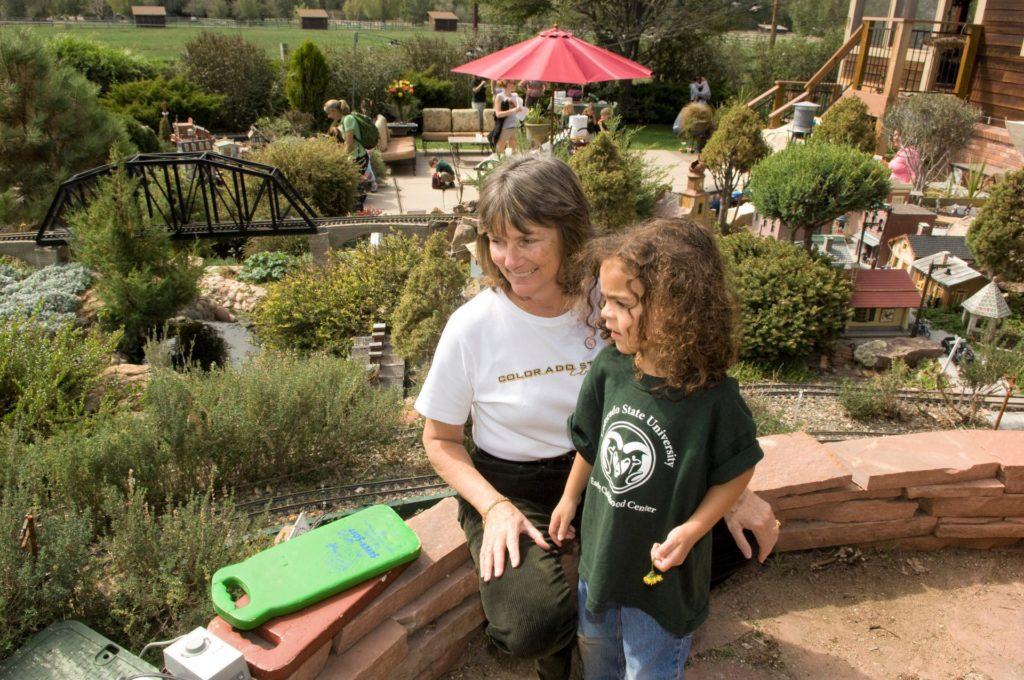 Prue Kaley showing a child her train garden