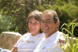 Prue Kaley and Mark goldrich smiling sitting in their garden