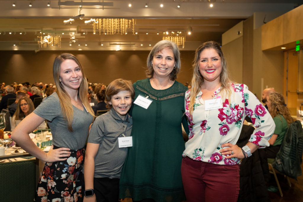 Kaley Goldrich (left) Wyatt Dennis (second to left) Shelly Goldrich (second to right) and scholarship recipient smiling in a group photo at the 2019 scholarship dinner