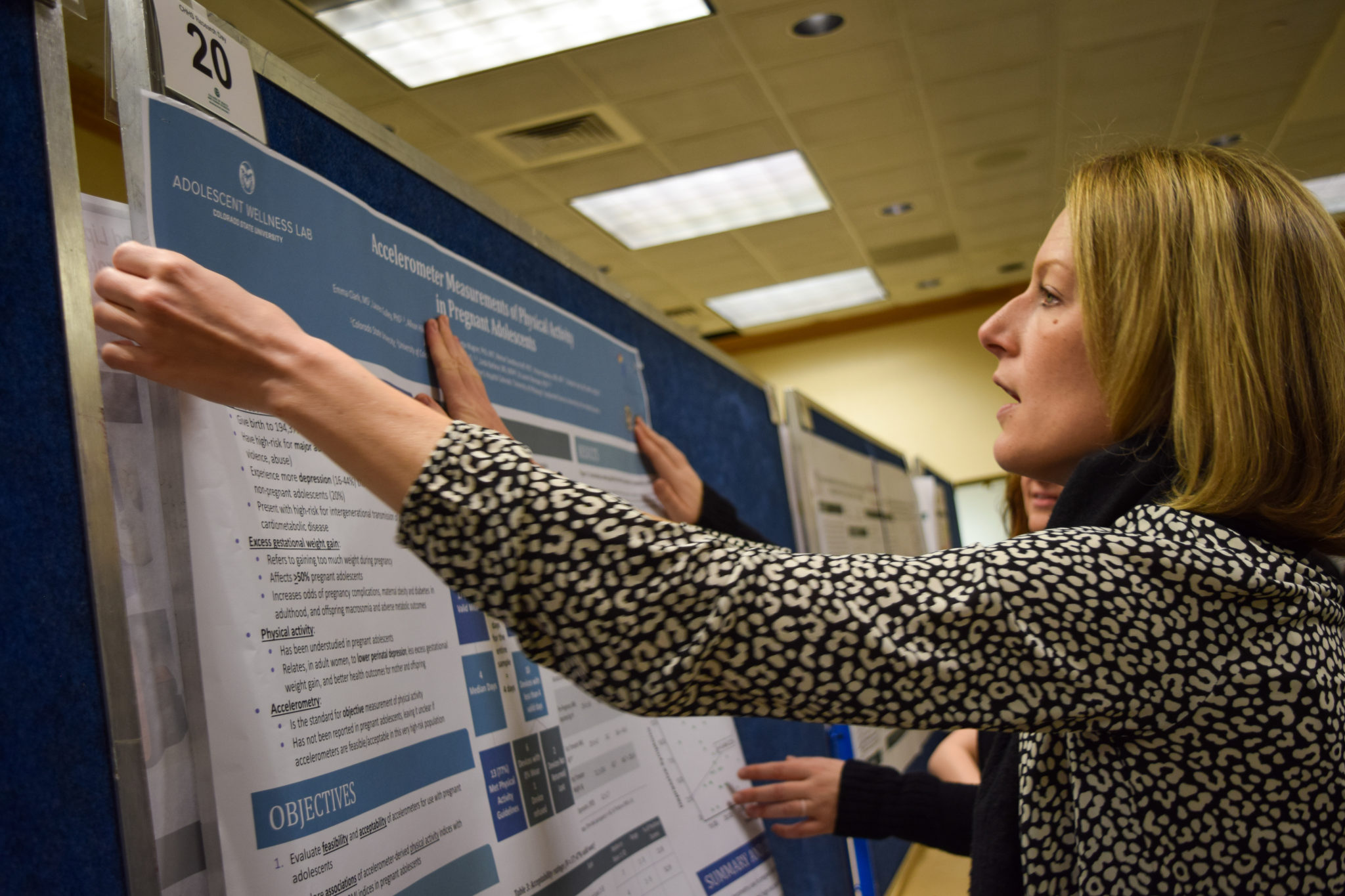 Woman tacks a poster to a presentation board.