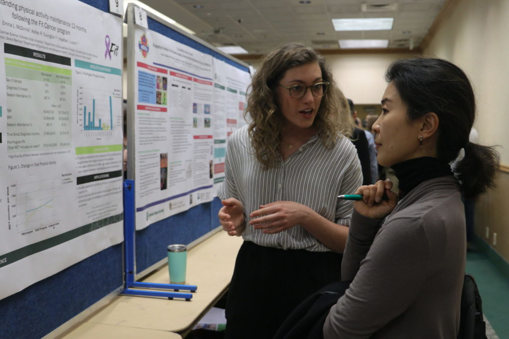 Research presenting the FitCancer poster to a judge at the 2020 Research Day