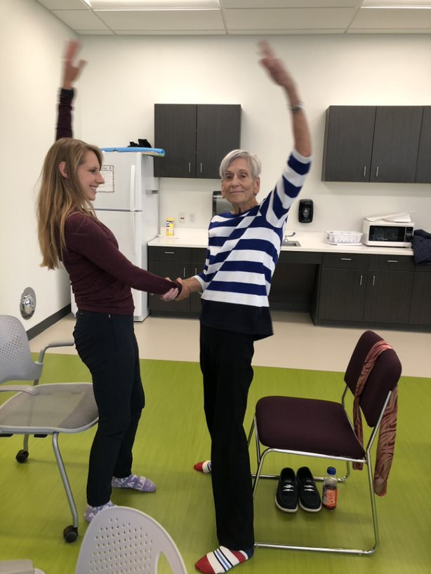 Occupational therapy student and older women stretching and dancing