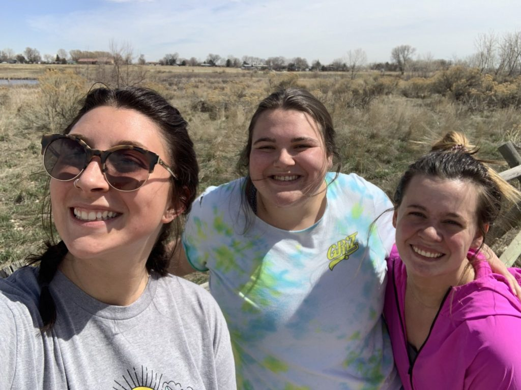 Three young women, Rebecca Rathburn and her roommates, pose for a photo outside on a trail.
