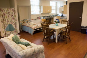 Classroom adapted like an apartment with living room and bedroom furniture and shower
