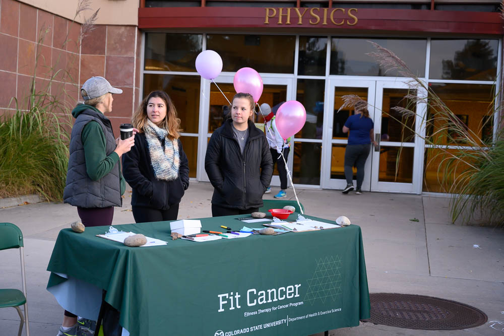 Three women standing at the FitCancer table during the 2019 Homecoming 5k race