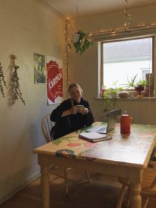 Alea Schmidt enjoying a cup of coffee at her kitchen table working on homework at home