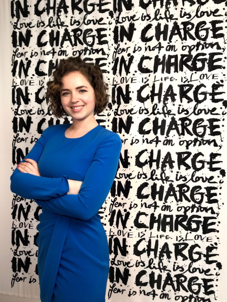"""Isabelle Clement standing in professional headshot in a blue dress in front of a background that reads """"In charge"""""""
