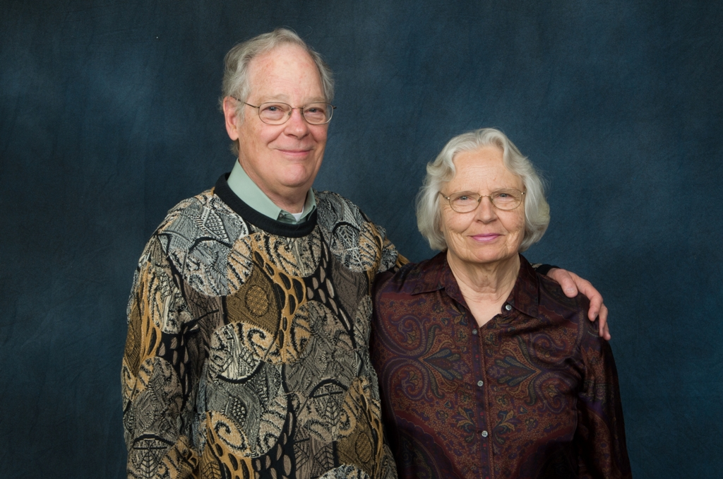 Man and woman stand for a portrait with their arms around each other