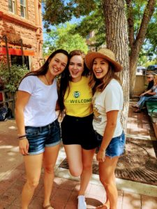 Isabelle Clement standing with friends wearing a Ram Welcome shirt