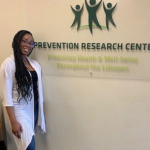 Joycey SaintJour standing in front of the Prevention Research Center.