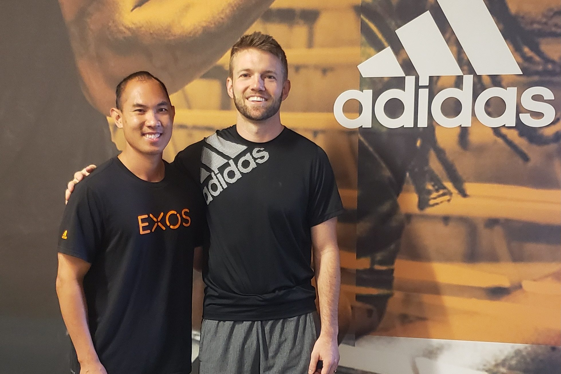 Two men pose in front of Adidas banner