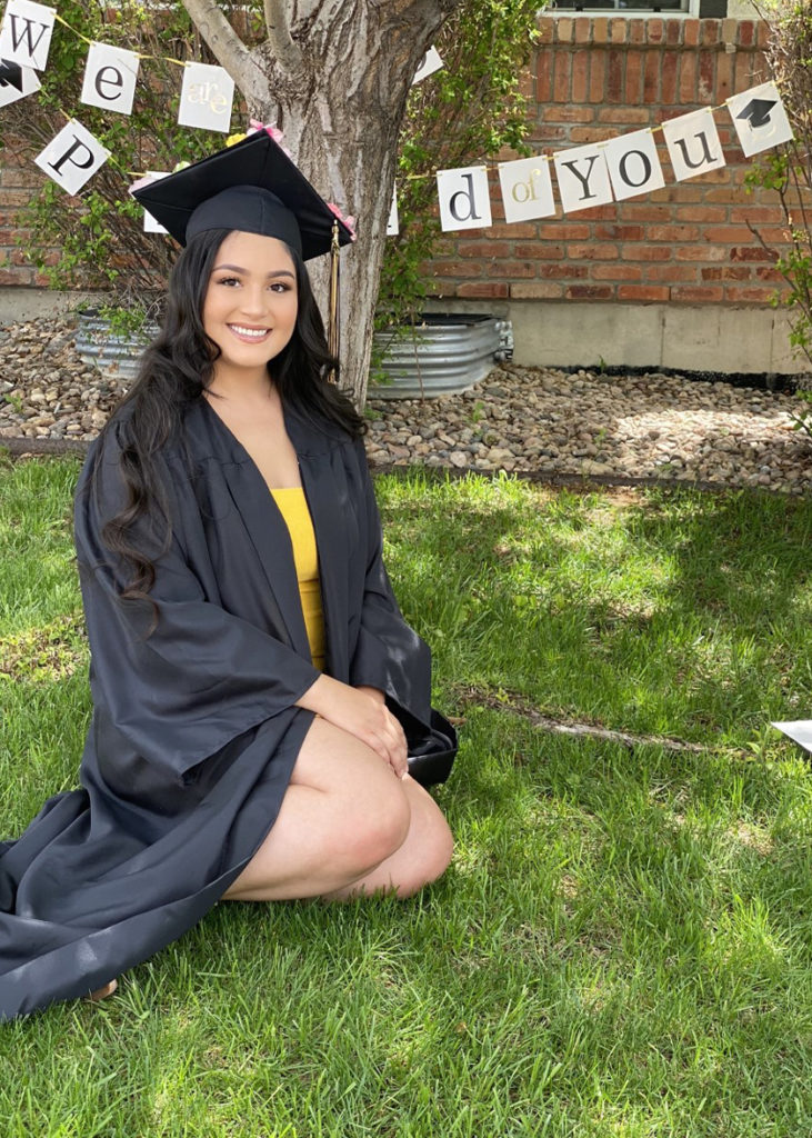 Bianca Villa in her graduation regalia on a green lawn.
