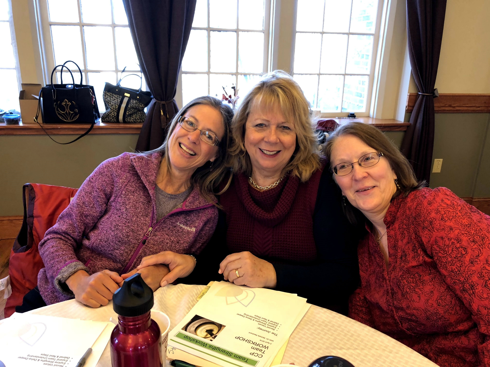 Deb Spotts sitting at a table with two co-workers