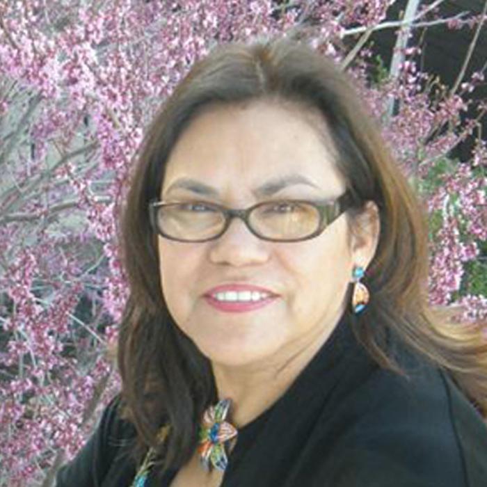 Dra. Salazar seated near a Japanese cherry blossom.