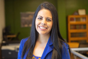 Jessica Gonzalez-Voller smiles into camera while wearing bright blue blazer and standing in front of green wall