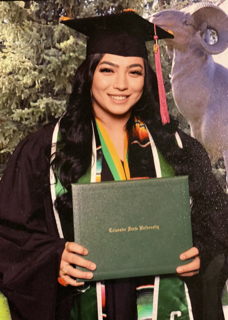 Jennifer Gomez stands in her commencement regalia holding her degree.