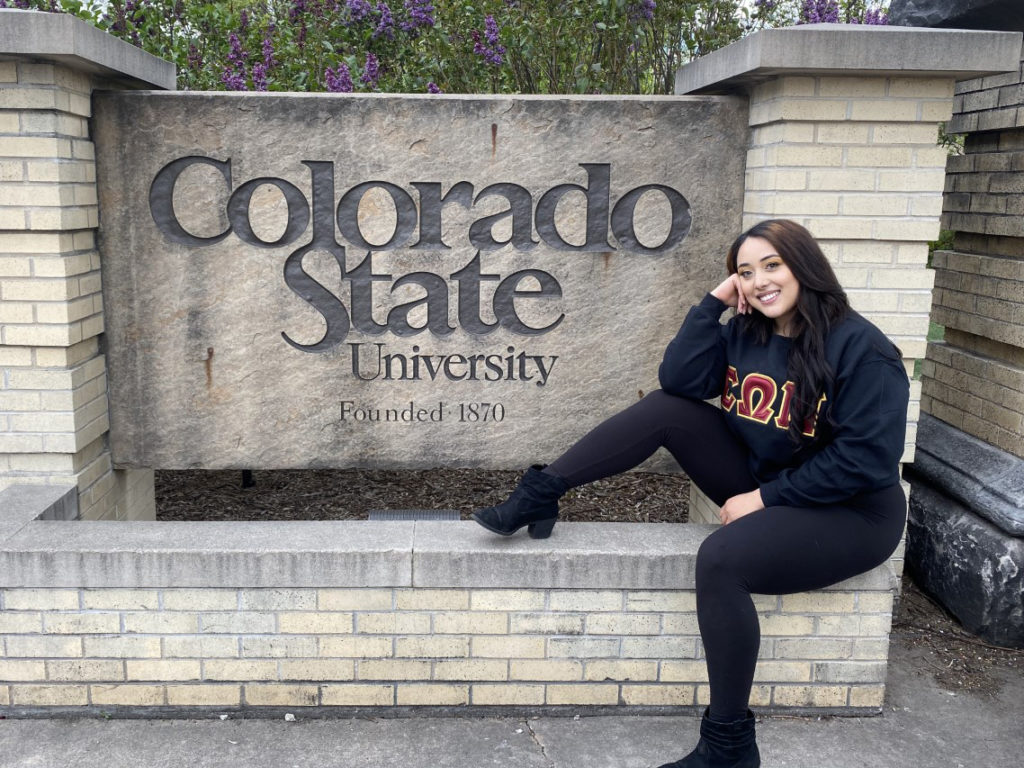 Jackie Terrazas seated near the entrance of Colorado State University in a black crewneck sweatshirt and black denim jeans.