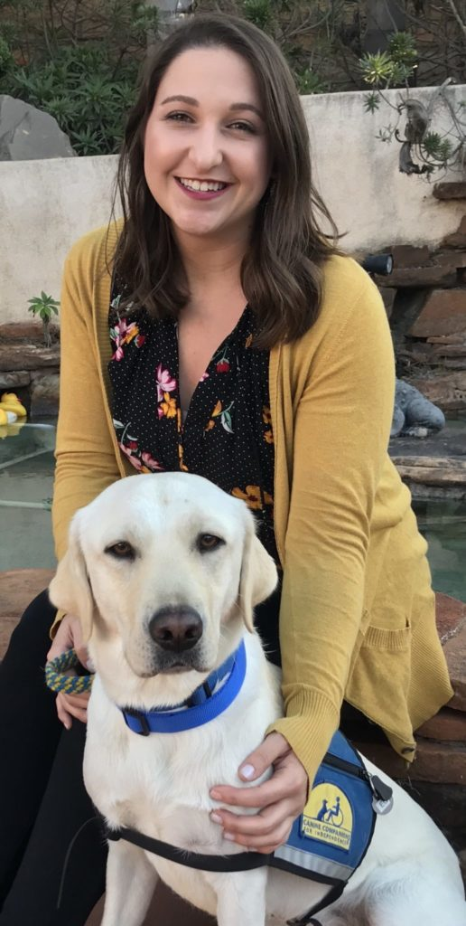 kerri rodriguez sitting together with a yellow labrador service dog and smiling