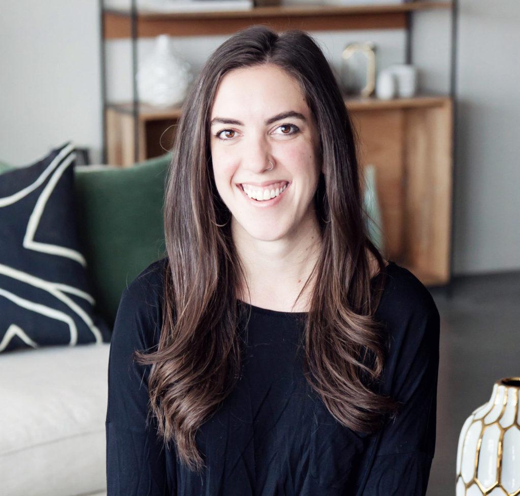 Lauren Cox smiles in a model living room.