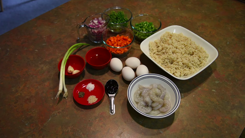 Ingredients for a fried rice recipe are placed on a wooden table. Green onion, red onion, shrimp, rice, and eggs.