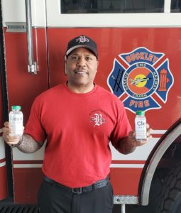 fire station personnel holding donated bottles of hand sanitizer