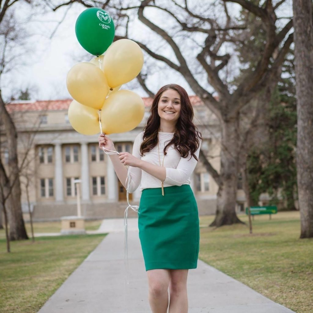 Jessica Teal holds green and gold balloons on the CSU campus.