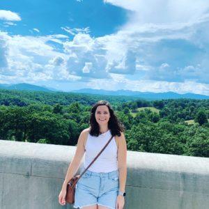 Lauren Nale standing on walkway in front of tree line natural area