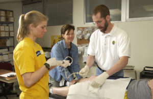 Matt Hickey and two students perform a muscle biopsy in 2002 for a research study examining the effect of protein on muscle protein synthesis.