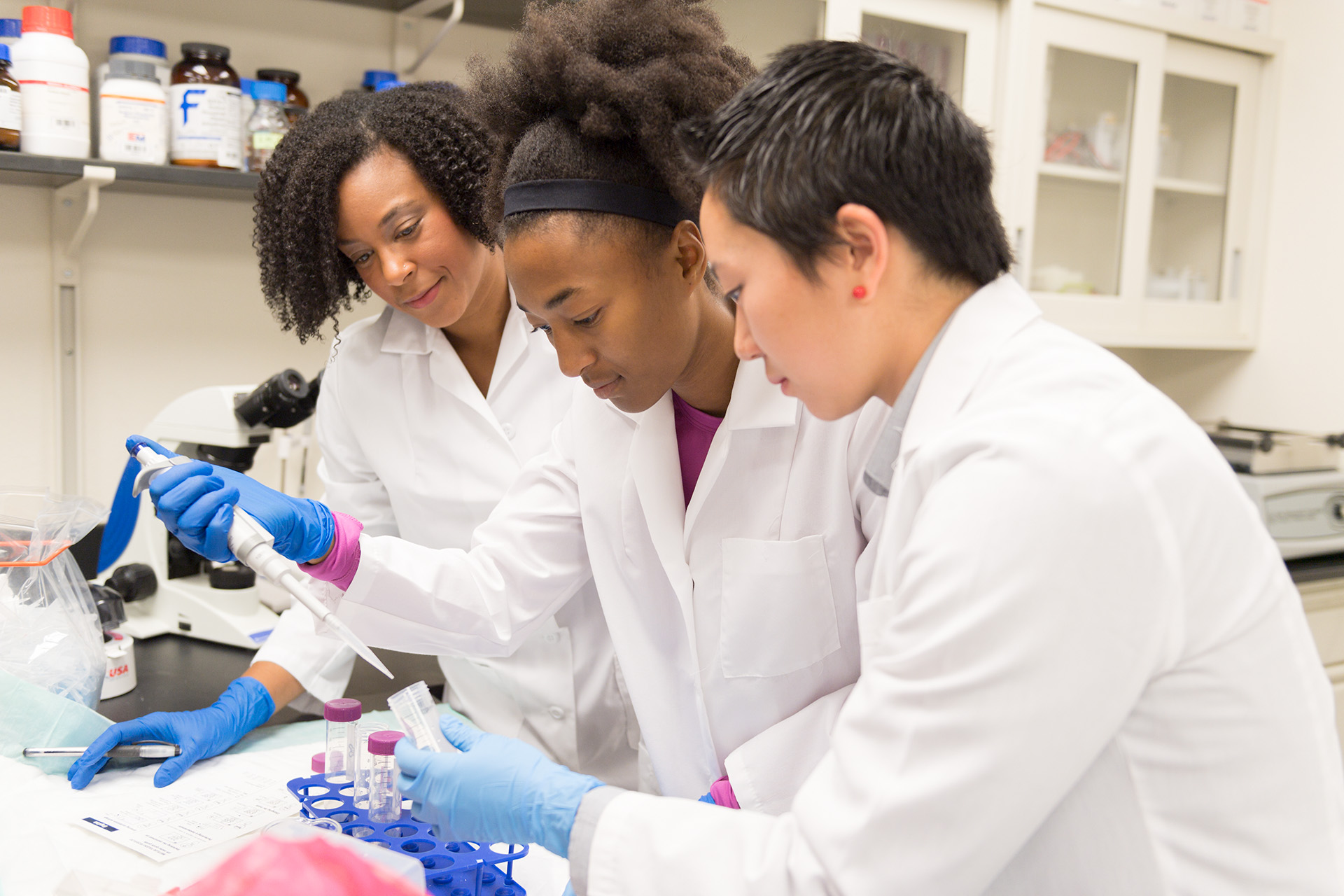 Michelle Foster and two other researchers in a lab using lab tools