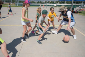 Campers and the counselor play a game of basket ball outdoors