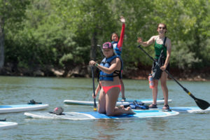 Three campers paddle boarding