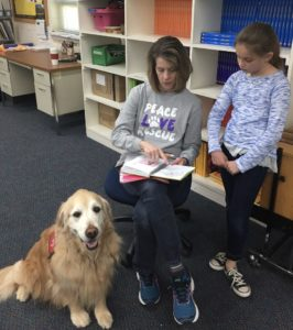 Zuri and handler Brenda working on reading a book with a school student