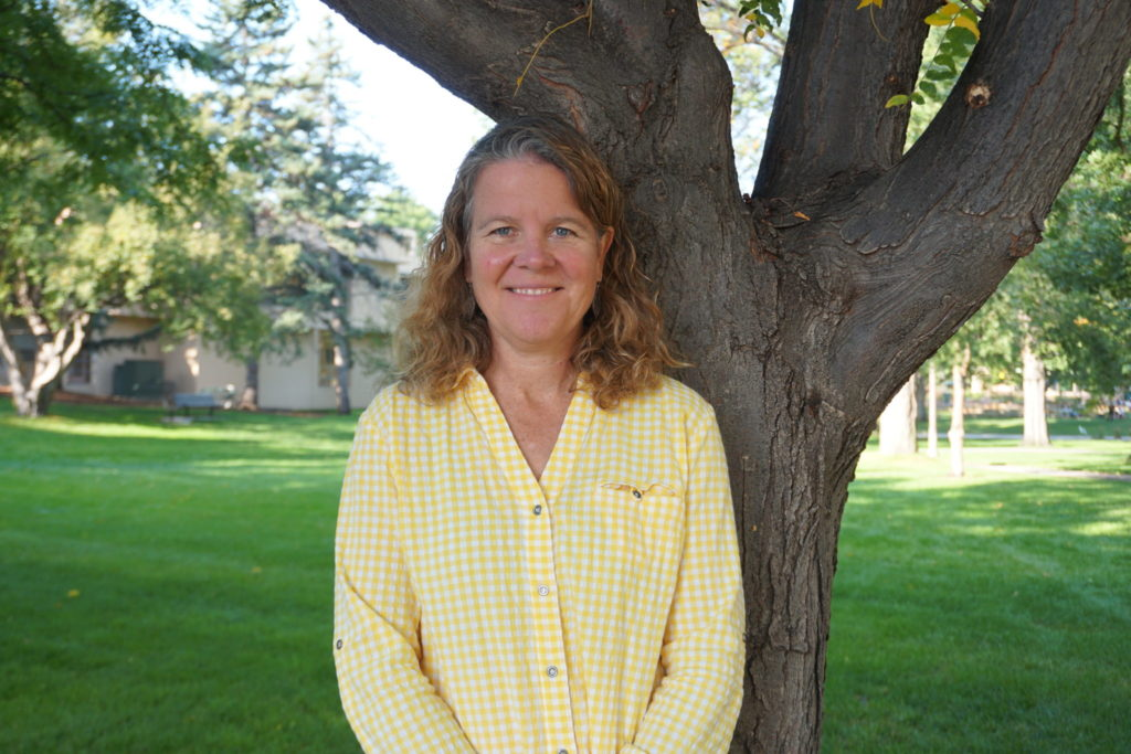 Julie Rieker standing next to a tree for a portrait photo