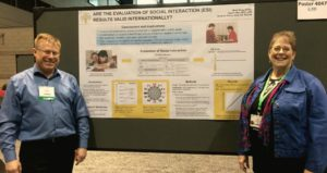 Berg Berg with his advsier, Karen Atler, by his research poster at the AOTA conference