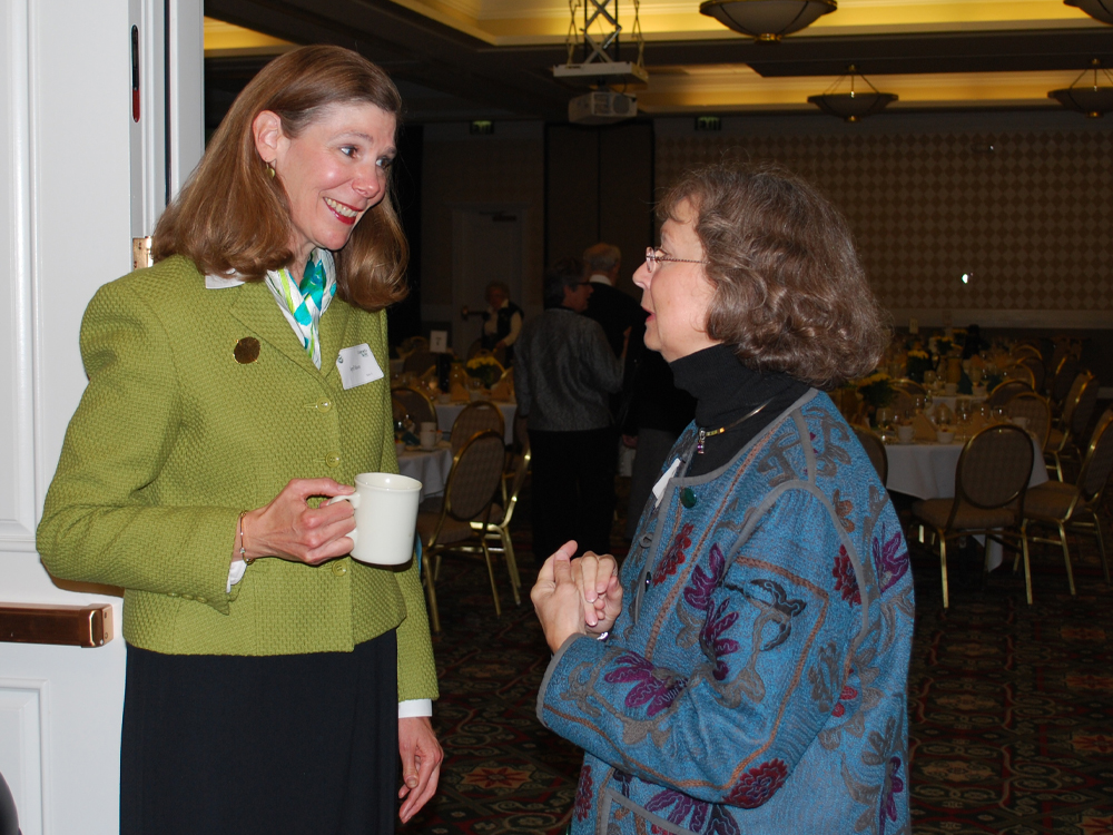 April Mason holds a mug of coffee and speaks with a colleague at an event.