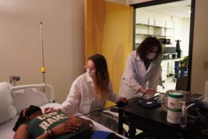 Graduate student Allegra (left) Lauren Grabos (middle) and Brayden Smith (right) measuring vitals on Allegra.