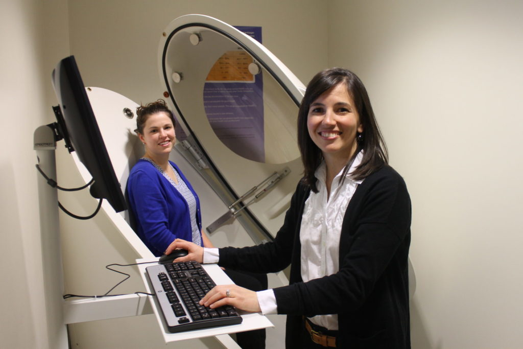 Lauren Shomaker (right) using the bod pod machine.