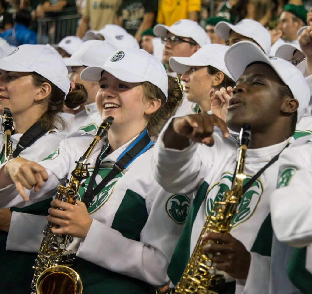 Bee Pettner smiles in her CSU Marching Band attire while holding her saxophone among a crowd of her marching band colleagues.