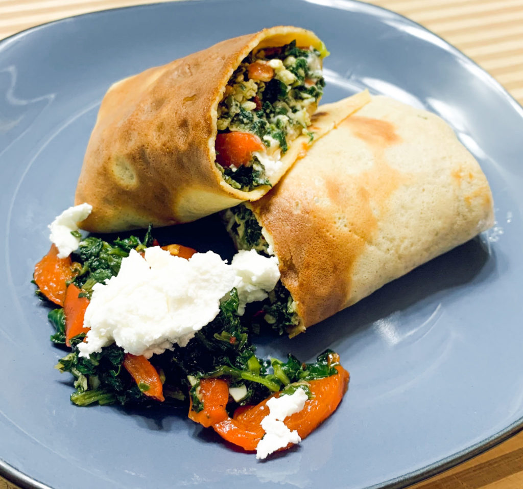 Savory, vegetable-filled crepe on a blue plate.