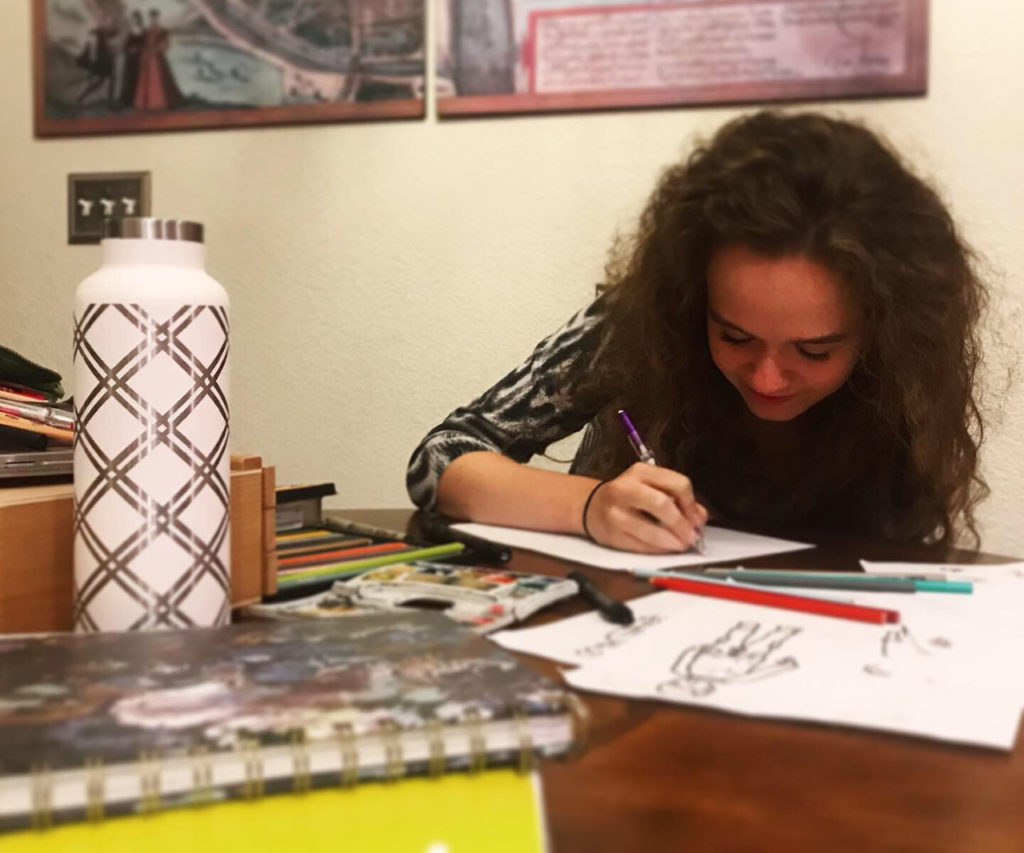 "Isabella ""Bee"" Pettner works in her home studio on garment designs. She is sketching on a wooden table."