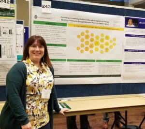Julie standing by her research poster