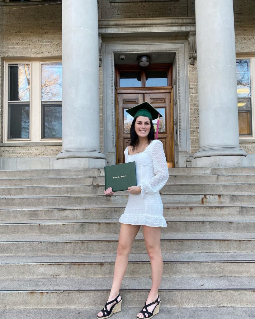 Julie Phillips, wearing a white dress and a green mortar board, stands in front of the CSU Administration Building holding her green diploma portfolio.